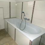 Fliesenverlegung bei einer Badewanne mit Mosaiksteinen